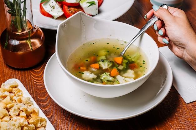 La donna mangia la minestra di verdura con sedano e patate di piselli di broccoli