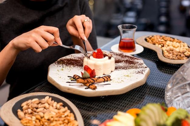 La donna mangia la torta della caramella gommosa e molle con la fragola