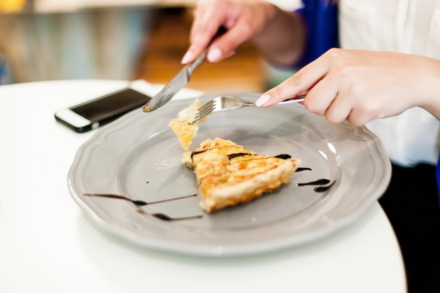 La donna mangia una torta nel caffè