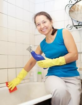 La donna matura sorridente pulisce la vasca da bagno