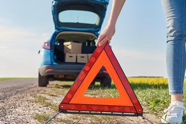 La donna mette un segnale di arresto di emergenza vicino all'automobile rotta sulla strada