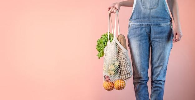 La donna moderna è in possesso di un sacchetto di spago con gli acquisti