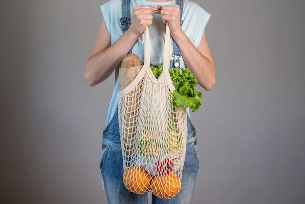 La donna moderna in jeans sta tenendo una borsa a tracolla con gli acquisti