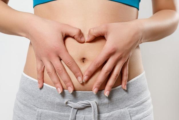 La donna mostra il cuore di gesto di due mani sul suo stomaco. su bianco. concetto di salute delle donne, gravidanza precoce