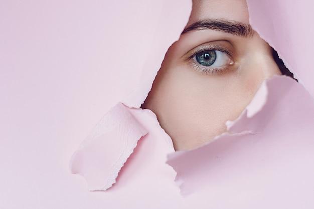 La donna mostra l'occhio attraverso la parete rotta