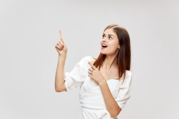 La donna mostra un dito vicino sul vestito da sorriso copia spazio