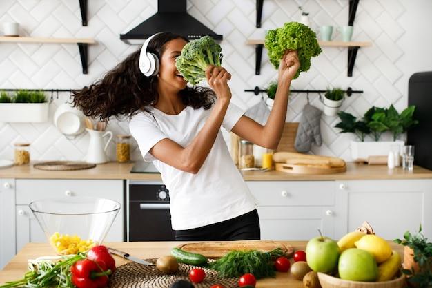 La donna mulatta sorrisa in grandi cuffie senza fili sta ballando con foglie di insalata e broccoli sulla cucina moderna vicino al tavolo pieno di frutta e verdura
