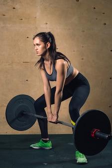La donna muscolare in una palestra che fa gli esercizi pesanti con il bilanciere