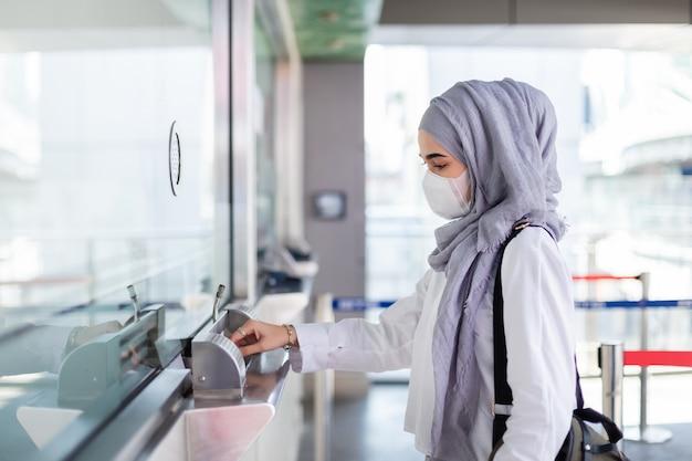 La donna musulmana asiatica che indossa la maschera medica per impedisce la polvere e il virus dell'infezione che cammina dentro compra il biglietto del passeggero alla stazione ferroviaria elettrica. concetto di coronavirus (covid-19).