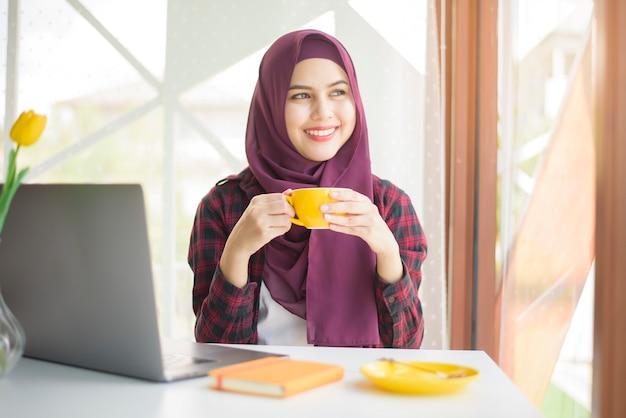 La donna musulmana con l'hijab sta lavorando con il computer portatile in caffetteria