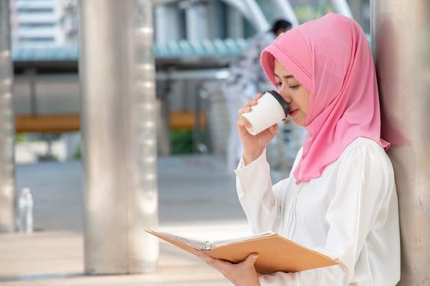 La donna musulmana sta bevendo la bevanda calda mentre legge il libro.