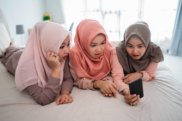La donna musulmana tre che si trova e gode di usando lo smartphone sul letto