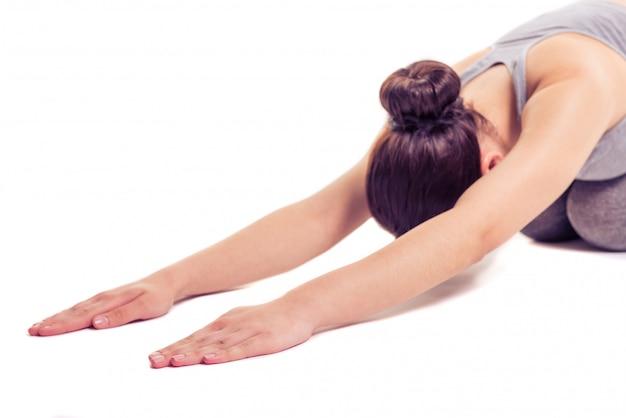 La donna negli sport indossa l'allungamento mentre fa l'yoga.