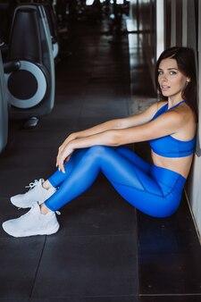 La donna nel riposo comodo di sport ha peso contro la parete, concetto finito di energia della ragazza di allenamento