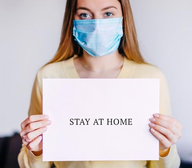 La donna nella maschera medica che posa tenendo il testo dello strato del libro bianco resta a casa
