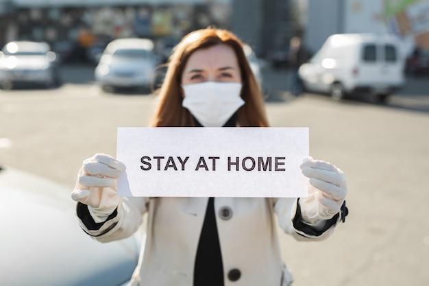 La donna nella mascherina medica protettiva tiene un cartello