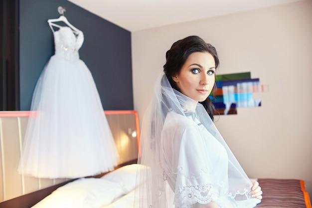 La donna nella stanza in un accappatoio sta i vestiti da sposa