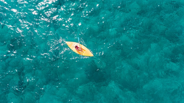 La donna nuota su un kayak sportivo in un mare cristallino esotico turchese.