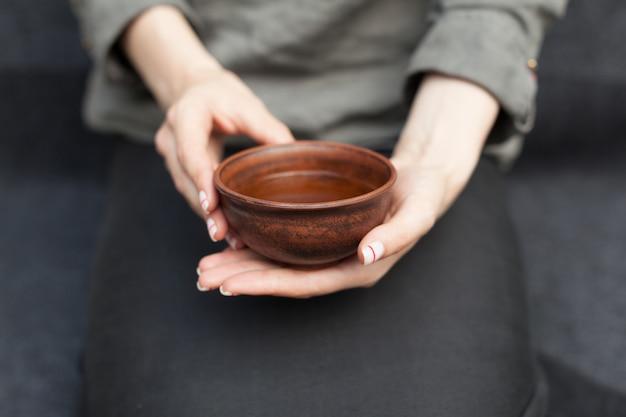La donna offre tè caldo in una tazza di ceramica vintage.