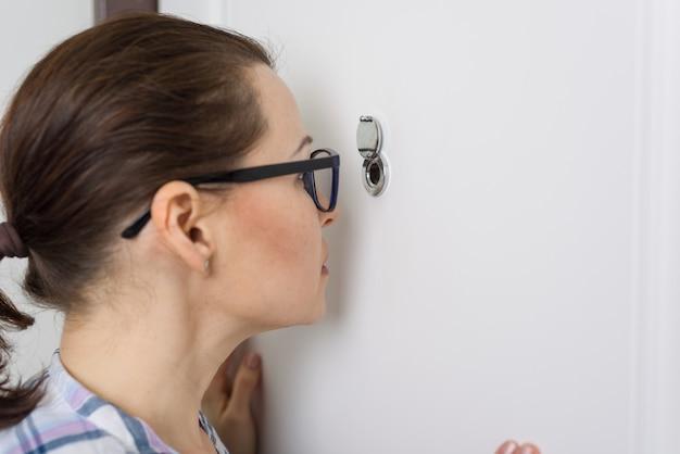 La donna osserva attraverso lo spioncino
