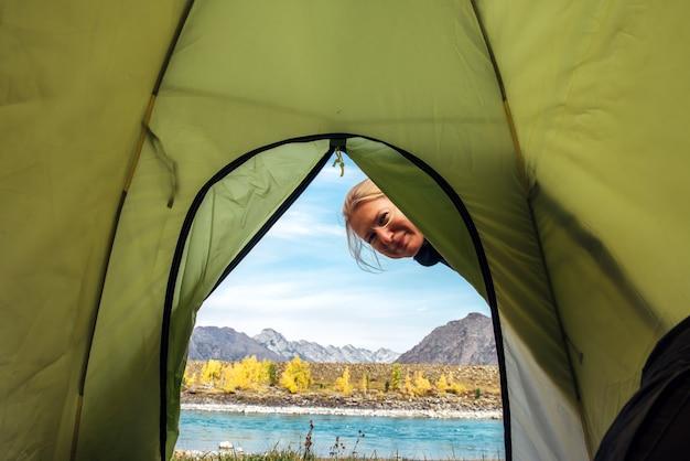 La donna osserva dentro la tenda verde e sorride. vista dall'interno della tenda sul fiume e sulle montagne il giorno soleggiato di autunno.