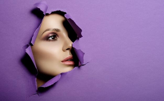 La donna osserva in foro carta viola colorata, trucco e cosmetici di bellezza di moda, salone di bellezza