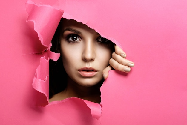 La donna osserva nel buco colorato carta rosa, trucco di bellezza moda e cosmetici, salone di bellezza