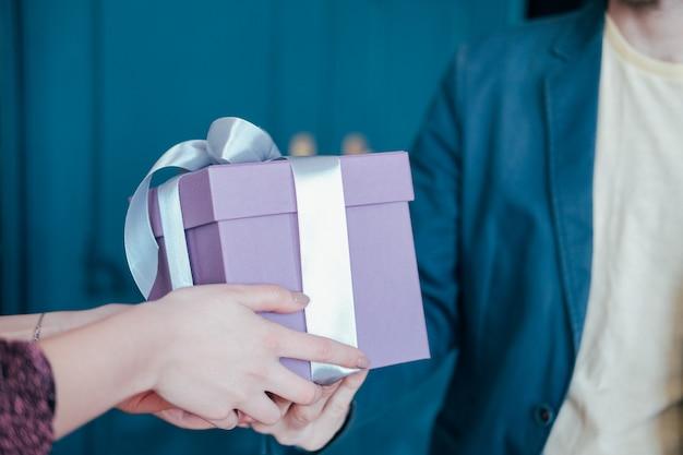 La donna ottiene il contenitore di regalo con il nastro d'argento grigio dal giovane uomo attracrive su fondo blu