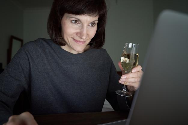 La donna parla online in chat video con gli amici e beve vino.