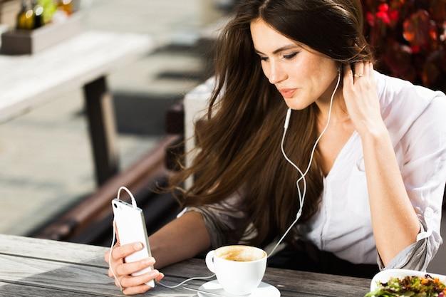 La donna parla via le cuffie sul telefono