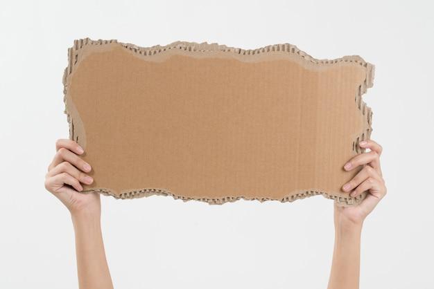 La donna passa il cartone della tenuta con lo spazio della copia isolato su bianco