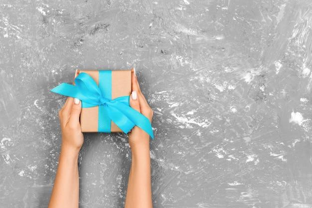 La donna passa il contenitore di regalo della tenuta con il nastro blu