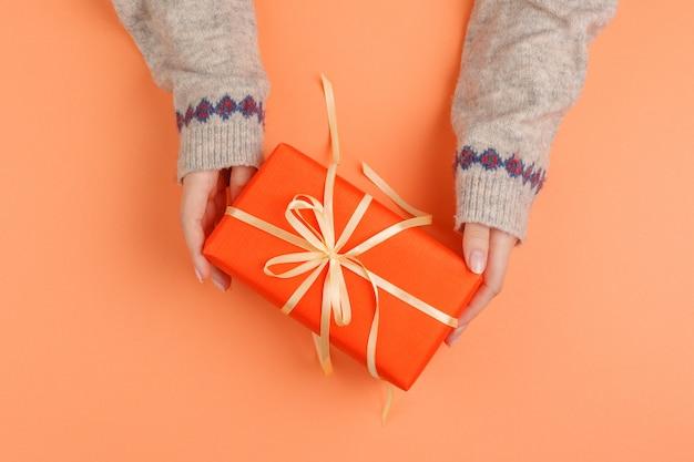 La donna passa il contenitore di regalo della tenuta su fondo arancio