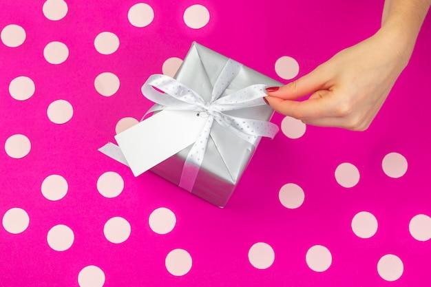 La donna passa il contenitore di regalo della tenuta su fondo rosa