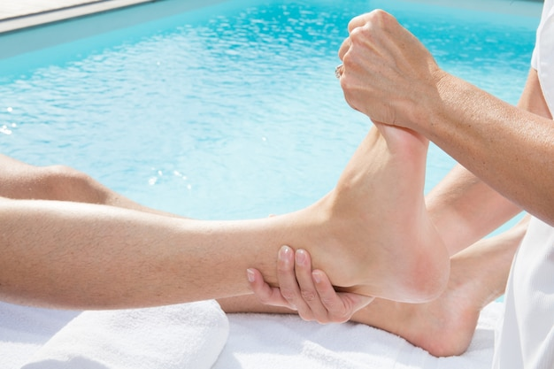 La donna passa il massaggio del piede dell'uomo su una tavola medica vicino allo stagno nel centro della stazione termale