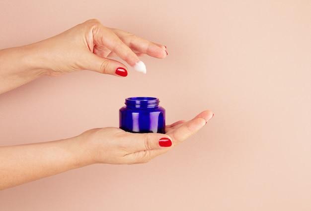 La donna passa il prodotto di cura di pelle della tenuta