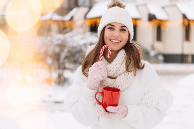 La donna passa in guanti che tengono una tazza accogliente con cioccolata calda, tè o caffè e un bastoncino di zucchero.