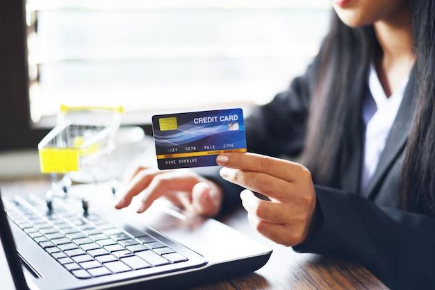 La donna passa la carta di credito della tenuta e che per mezzo del computer portatile per l'acquisto online in un carrello della tavola dell'ufficio / i lavoratori che pagano il pagamento online del portafoglio dei soldi della tecnologia
