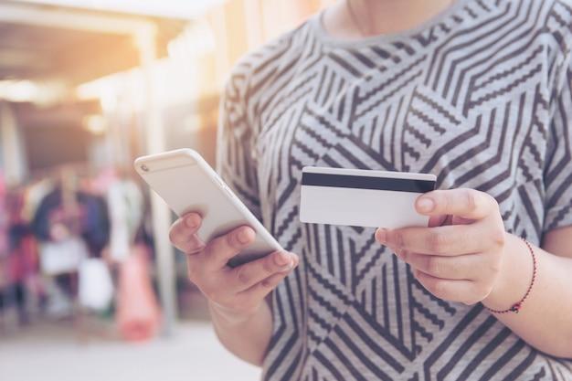 La donna passa la carta di credito della tenuta e facendo uso dello smart phone per il pagamento online, lo shopping online,