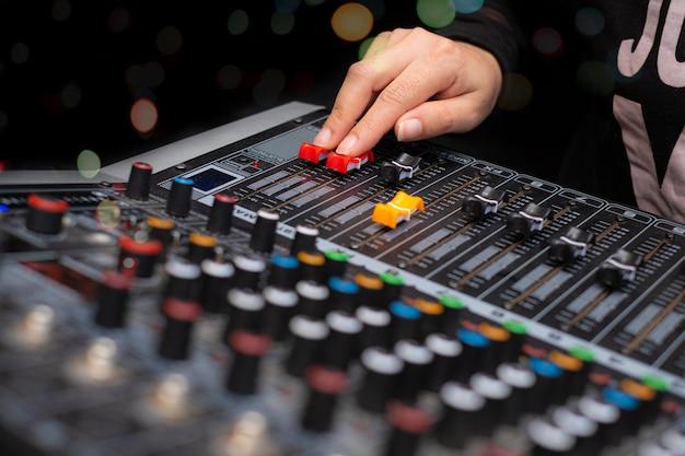 La donna passa la miscelazione dell'audio dall'analogo del miscelatore del suono