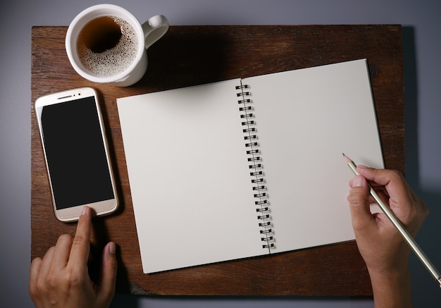 La donna passa la scrittura in taccuino in bianco dalla matita e da uno smartphone di tocco delle mani