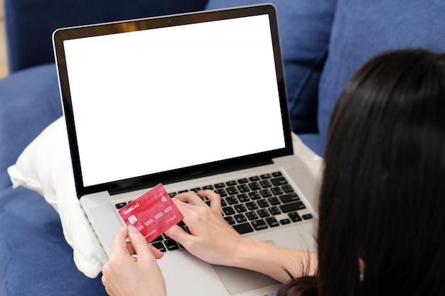 La donna passa la tenuta della carta di credito e il computer portatile di battitura a macchina con lo schermo in bianco. concetto di pagamento bancario internet