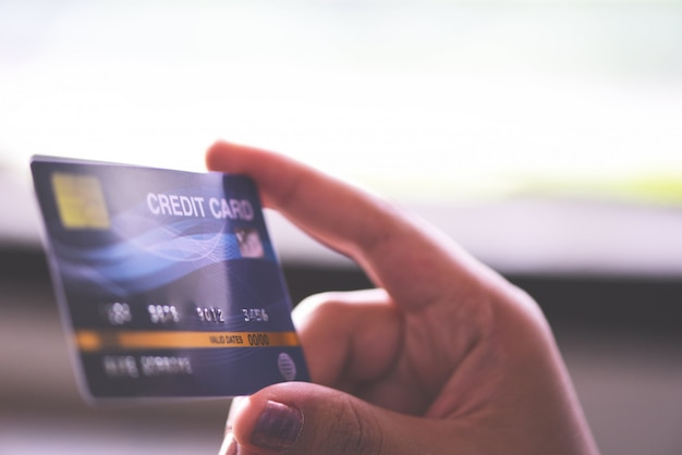 La donna passa la tenuta della carta di credito per l'acquisto online a casa. persone che pagano pagamento online con tecnologia denaro portafoglio.