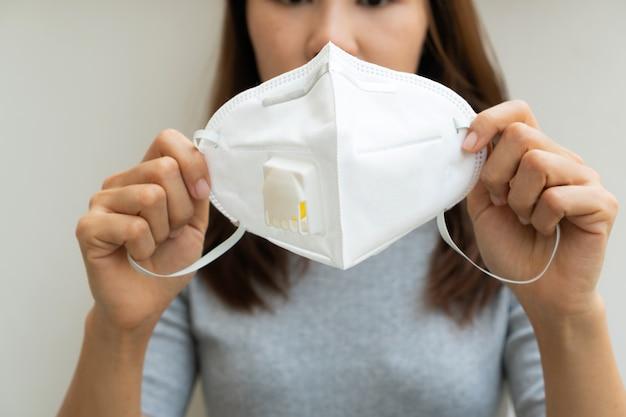La donna passa la tenuta della maschera protettiva per prevenire l'inquinamento e il concetto della malattia.