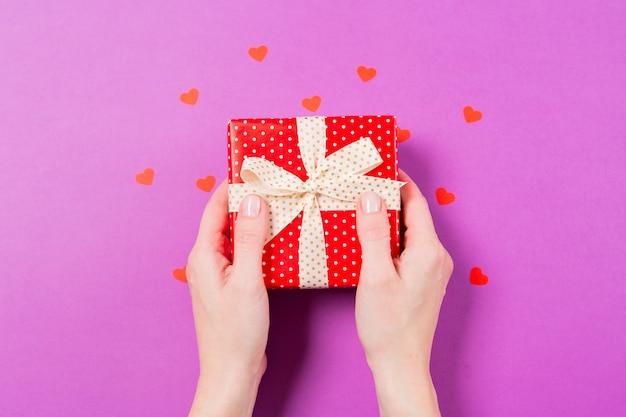 La donna passa la tenuta della scatola rossa del presente del regalo con piccolo cuore rosso intorno su fondo porpora. concetto di san valentino.