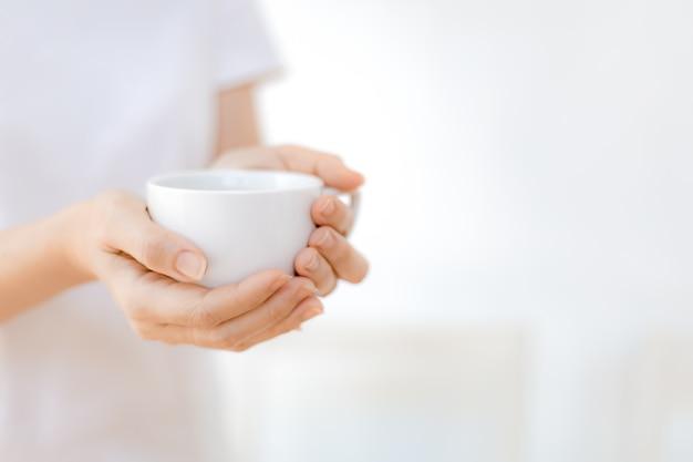 La donna passa la tenuta della tazza di caffè bianco