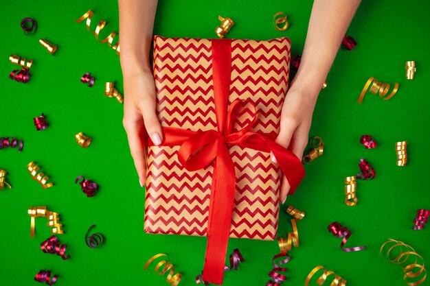 La donna passa la tenuta della vista superiore del contenitore di regalo