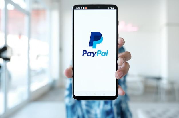 La donna passa lo smartphone della tenuta con le app di paypal sullo schermo. paypal è un sistema di pagamento elettronico online.