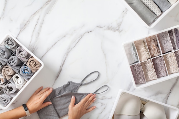 La donna passa ordinatamente piegando la biancheria intima e ordinamento negli organizzatori del cassetto su fondo di marmo bianco