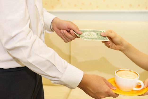 La donna passa una banconota del dollaro per la punta al cameriere dopo il latte ricevuto.